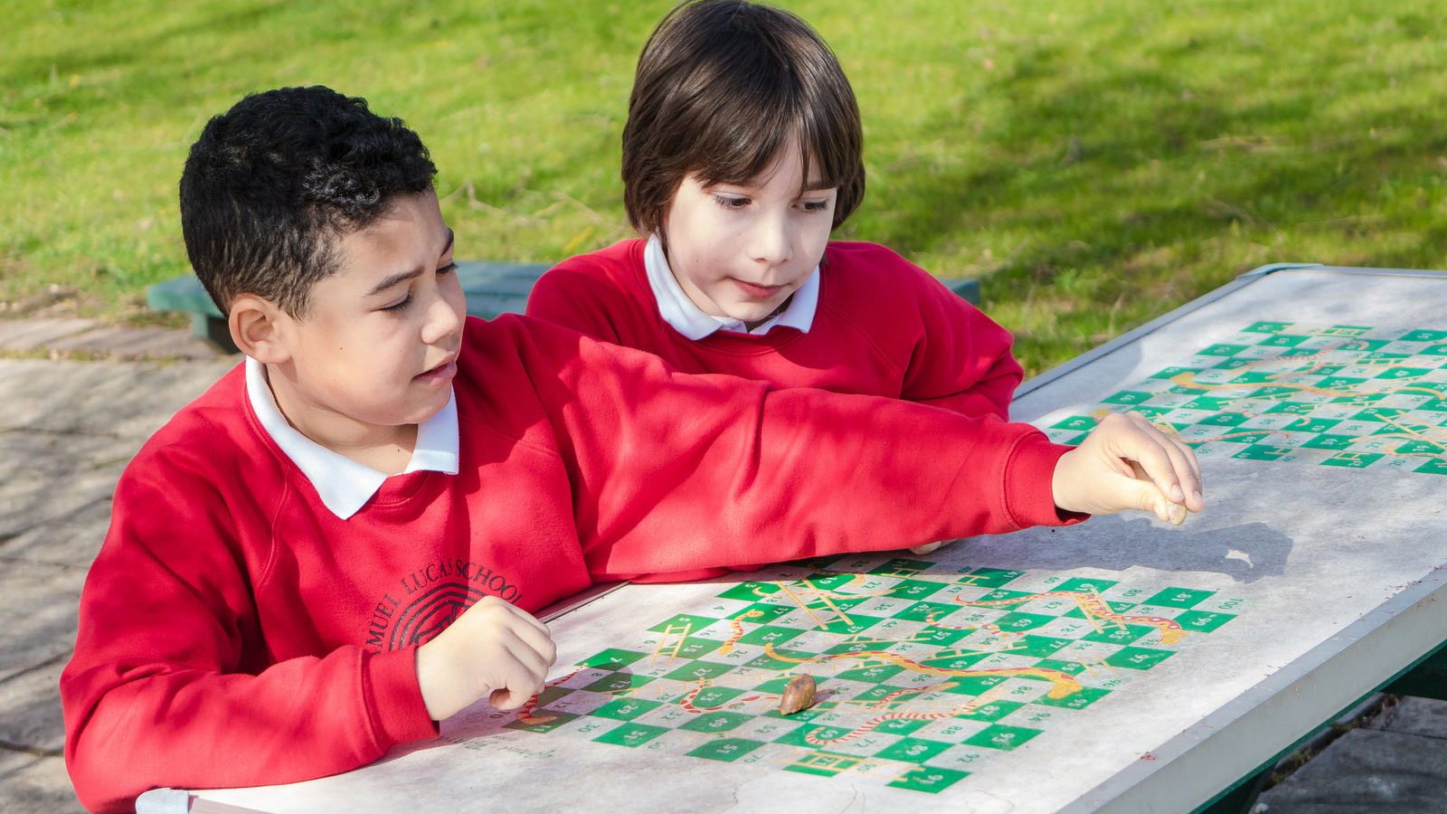 Boys playing outdoor snakes and ladders