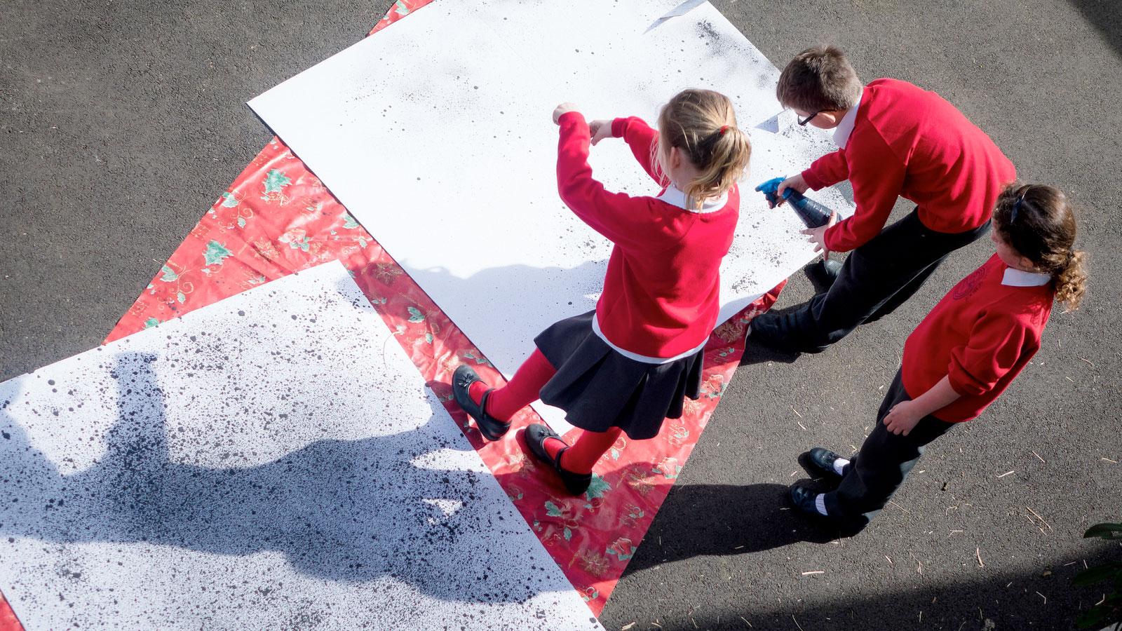Children spraying paint outside