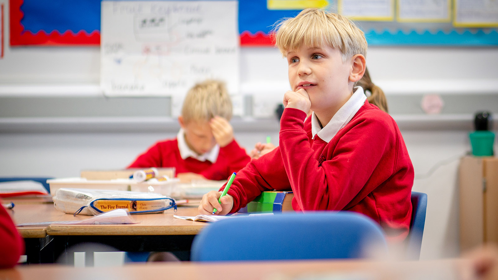 Boy at desk in school classroom holding pen looking at teacher