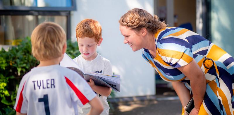 Teacher smiling as child reads their work